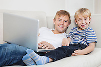 Portrait of happy boy with father using laptop on sofa