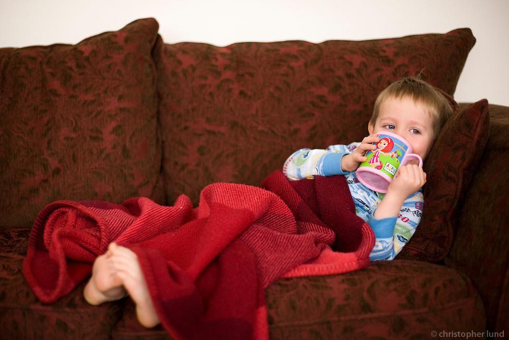Young boy laying in sofa in his pajamas, drinking from a Lazy Town cup. Ari Carl veikur heima. Liggur upp í sófa með teppi og drekkur úr Latabæjarglasinu sínu.