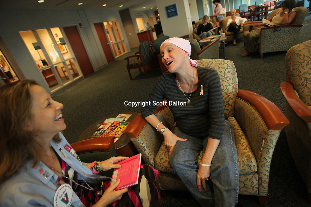 "Kelli Jones, a breast cancer patient, receives a visit from Susan Rafte, left, a breast cancer survivor and a ""Pink Ribbon Volunteer"" in the waiting room of the breast cancer division of the MD Anderson Cancer Center in Houston, TX on October 5, 2009. (Photo/Scott Dalton)"