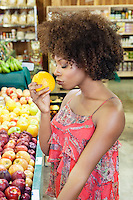 Side view of African American woman smelling fresh orange at supermarket