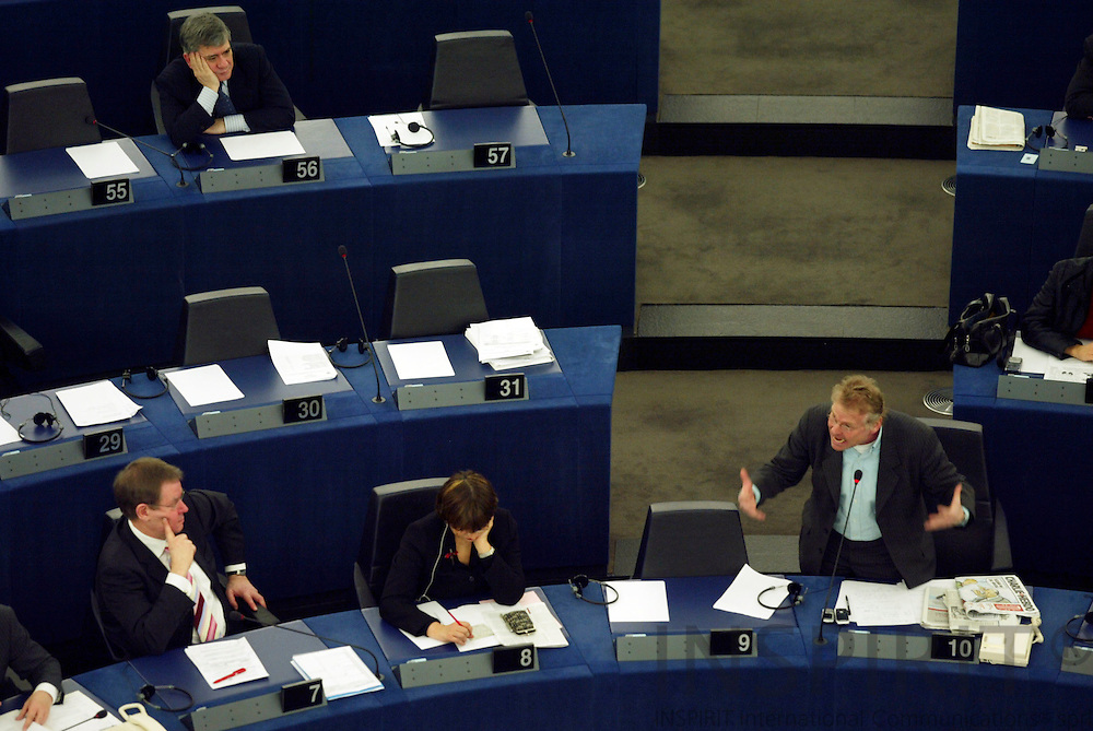 "STRASBOURG - FRANCE - 15 FEBRUARY 2006 -- MEP Daniel Marc COHN-BENDIT (R) during the debate on the Danish Muhammed Cartoons speaking to Danish MEP Poul Nyrup RASMUSSEN (L) and the Parliament. On his left side a copy of the French newspaper Charlie Hebdo with the Danish cartoons. PHOTO: ERIK LUNTANG / ..This image is delivered according to terms set out in ""Terms - Prices & Terms"". (Please see www..com for more details)"