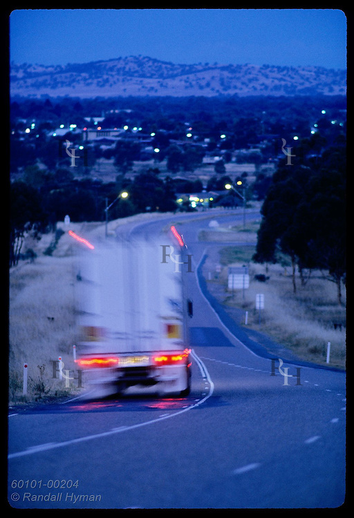 Truck speeds down highway in blur of tailights at dusk outside town of Wagga Wagga; (v) NSW. Australia