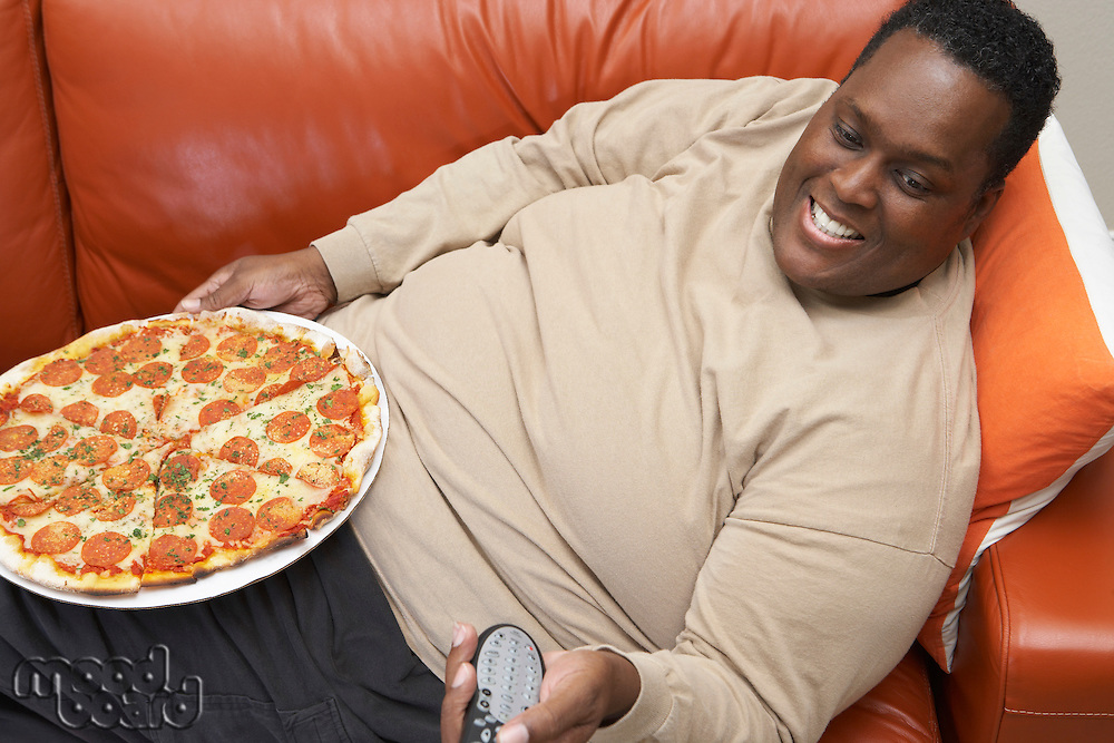 Man watching tv with pizza on lap