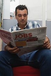 Bulgarian man looking in the job section of the newspaper for work,