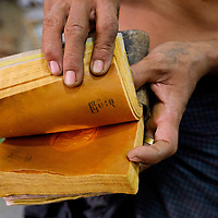 A man working in a gold leaf workshop shows the flattened gold pieces that are placed in between bamboo sheets for pounding in Mandalay, Myanmar (Burma).