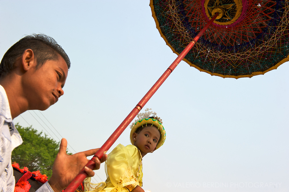A boy during the buddhist novitiation ceremony (Shinbyu) dressed in silk, shielded from the sun by an umbrella, is led on horseback. It symbolises Siddhartha departures from the Royal palace.