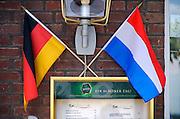 Duitsland, Elten, 15-6-2010In Elten, gemeente Emmerich vlak over de grens bij Arnhem en Zevenaar, staan vele nieuwe huizen die gebouwd en bewoond zijn door nederlanders. Nederlandse makelaars zijn aktief in deze markt. Duitsers klagen over de gebrekkige integratie, deelname aan het maatschappelijke en sociale leven, van de Hollanders. Verschillenden hebben hun huis alweer verkocht en zijn teruggegaan. Ook vinden er nogal wat echtscheidingen plaats. Het bouwen van een huis en de bouwkavel zijn goedkoper als in Nederland. Nederlandse en Duitse vlaggen naast elkaar vanwege het wereldkampioenschap voetbal in Zuid Afrika.Foto: Flip Franssen/Hollandse Hoogte