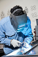Young man wearing welding mask while working in metal workshop
