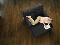 Mid-adult woman lying on sofa leafing through notebook view from above