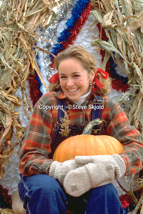 Girl age 17 on float in farmer costume at Anoka Halloween Festival.  Anoka Minnesota USA