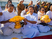 "02 JANUARY 2015 - KHLONG LUANG, PATHUM THANI, THAILAND: People pray with marigolds that would be put on the footpath for monks at Wat Phra Dhammakaya at the start of the 4th annual Dhammachai Dhutanaga (a dhutanga is a ""wandering"" and translated as pilgrimage). More than 1,100 monks are participating in a 450 kilometer (280 miles) long pilgrimage, which is going through six provinces in central Thailand. The purpose of the pilgrimage is to pay homage to the Buddha, preserve Buddhist culture, welcome the new year, and ""develop virtuous Buddhist youth leaders."" Wat Phra Dhammakaya is the largest Buddhist temple in Thailand and the center of the Dhammakaya movement, a Buddhist sect founded in the 1970s.   PHOTO BY JACK KURTZ"