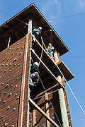 Ethan Scarberry, age 12, climbs the climbing wall to reach the zipline while his sister's boyfriend, Riley Braun, takes a photo from the top.
