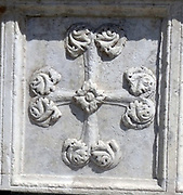External detail from a church in Florence, Italy. Stonework reliefs, sculptures, and aesthetic embellishments adorn the outside of this church in Florence. This image shows a cross.