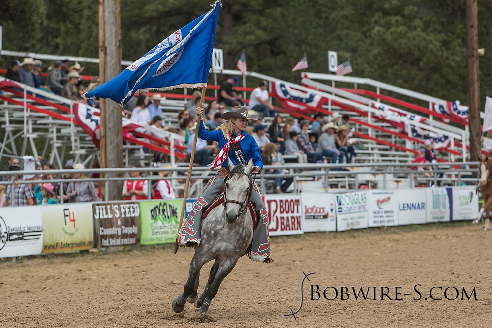 Elizabeth Stampede Attendant Brittany Vogl brings in the PRCA flag during the third performance of the Elizabeth Stampede on Sunday, June 3, 2018.
