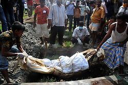 59591255 .Workers bury an unclaimed body at a mass funeral in Dhaka, Bangladesh, May 1, 2013.  The collapse of the eight-storey Rana Plaza building has left so far about 400 dead. Thousand of garment workers staged a procession to mark International Labour Day in Dhaka, demanding the death penalty for the owner of the building, 1 May, 2013. Photo by: i-Images.UK ONLY