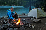 WA13239-00...WASHINGTON - Camper at the Big Beaver backcountry camp on Ross Lake enjoying an evening campfire; Ross Lake National Recreational Area.