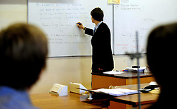 File photo dated 15/01/09 of a teacher writing on a white board, as a new report warns that teachers in England work some of the longest hours in the profession in the developed world, leaving them little time to develop their careers.