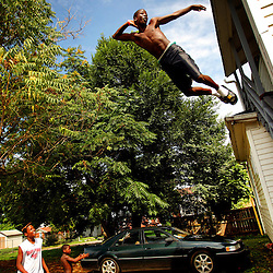 Kyle Green | The Roanoke Times<br /> August 12, 2009 Rasheed Whorley (age 13), takes a leap off a second story stairway onto a trampoline as friends, Jamar Preston (left, age 13), Malik Whorley (middle left, shirtless, age 8), and Demontrae Calloway (right, age 16), look on. The group assembled the trampoline at their house on SW13th Avenue two weeks ago, and have been playing on it everyday.