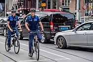 AMSTERDAM - twee ambetnaren van handhaving op een fiets in het centrum van amsterdam . controle  handhaving boete bekeuing parkeren , parkeer boete , fout , betalen , controle , kenteken , parkeerplaats , werk , werken ambtenaar ,  ROBIN UTRECHT