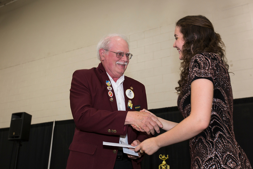 Sonja Eiseman, a graduating senior at the Pioneer Valley Chinese Immersion Charter School in Hadley, receives a scholarship from Roy Beals, Zone Chair of  the District 33 Y Massachusetts chapter of Lions International, at the 2018 PVCICS Awards Ceremony, 5/31/18.