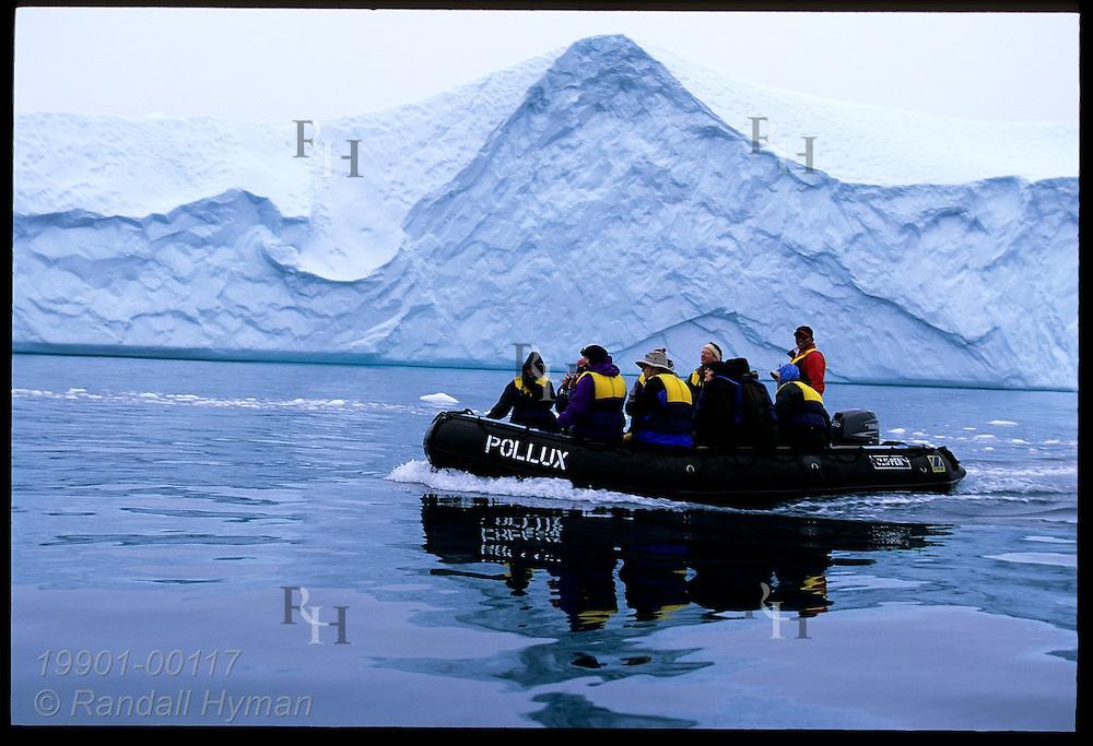 Tourists in rubber raft pass iceberg calved from Sermeq Kujalleq glacier in Disko Bay near Ilulissat Kangerlua Icefjord; Greenland