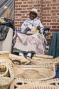 Gullah woman weaving sweetgrass baskets at the Historic Charleston City Market on Market Street in Charleston, SC.