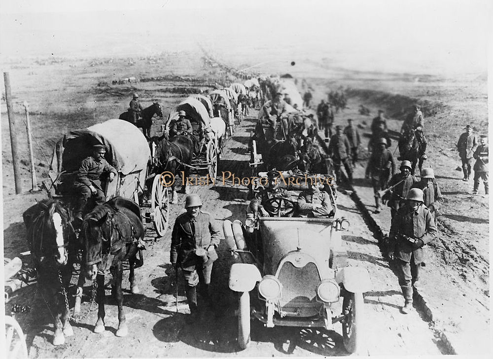 World War I 1914-1918: German offiers in a car in a long convoy of horse-drawn wagons. Soldiers walking along the road.
