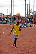 A young boy plays football barefoot on the streets of Ouagadougou, the capital of Burkina Faso. People playing football in any location big enough is a regular sight in capital.