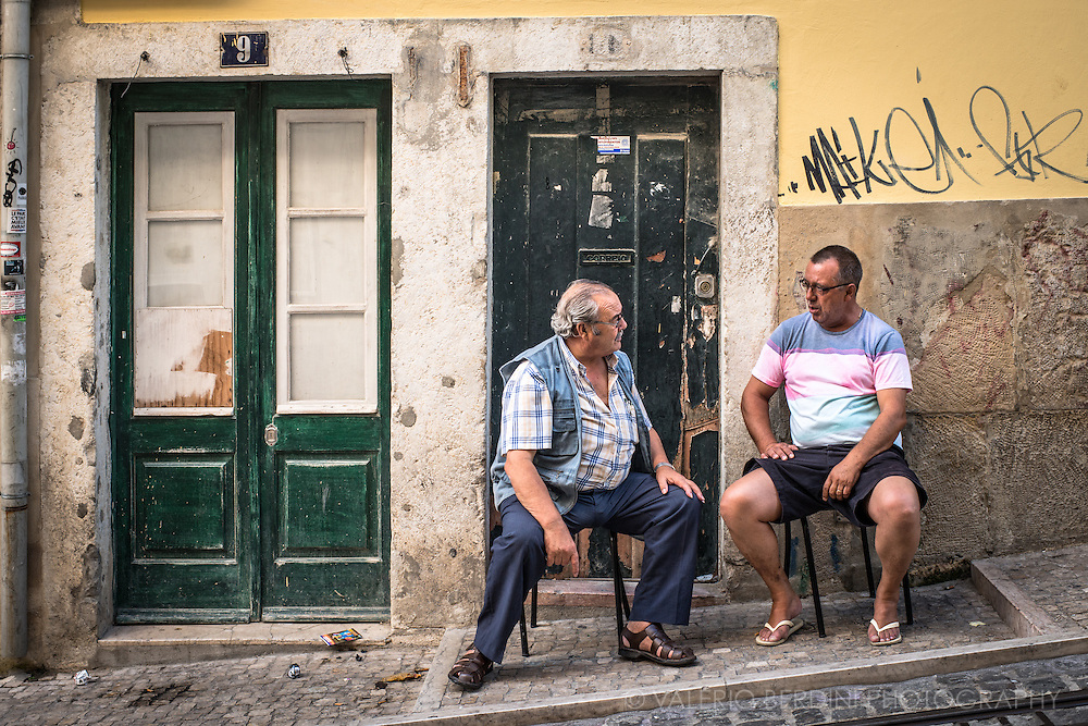 Two men in Calcada de Bica grande have a chat on the stairs along the steep funicolar way.