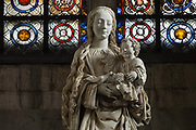 Virgin of the Grapes, or Vierge aux Raisins, detail, early 16th century statue of the Virgin and child with a bird eating a bunch of grapes, by Troyes School, in the Basilique Saint-Urbain de Troyes, or Basilica of Saint Urban of Troyes, a 13th century Gothic church in Troyes, Aube, France. The Virgin is crowned and smiling, standing on a crescent moon, and the Christ child holds a vine, while a bird eats the grapes. Behind is the grisailles stained glass window, 13th century, in the Chapelle de la Vierge, or Chapel of the Virgin. The windows were restored in 1879. The basilica was founded in 1262 under Pope Urban IV and consecrated in 1382, although the building was not completed until the 20th century. It is listed as a national monument. Picture by Manuel Cohen