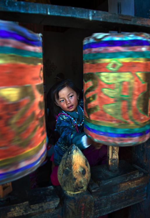 A girl spins the prayer wheels in Bumthang Bhutan.