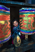 A girl spins the prayer wheels in Bumthang Bhutan.