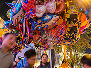 31 DECEMBER 2013 - BANGKOK, THAILAND: A balloon vendor looks for customers on New Year's Eve in Ratchaprasong Intersection in Bangkok. Hundreds of thousands of people pack into the Ratchaprasong Intersection in Bangkok for the city's annual New Year's Eve countdown. Many Thais go the Erawan Shrine and Wat Pathum Wanaram near the intersection to pray and make merit.     PHOTO BY JACK KURTZ