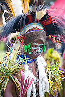 Woman dancing and wearing traditional tribal dress for the Goroka Show, Papua New Guinea. She is wearing a large headdress adorned with feathers and animal skins.