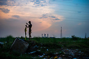 25th May 2014, Yamuna River, New Delhi, India. An elephant handler folds his clothes on a small island in the Yamuna river in New Delhi, India on the 25th May 2014<br /> <br /> Elephant owners (Mahouts) eke out a living in makeshift camps on the banks of the Yamuna River in New Delhi. They survive by giving rides to passers by and hiring the animals out for religious festivals, events and weddings, they also are involved in the illegal trade of captive elephants. The living conditions and treatment of elephants kept in cities in North India is extremely harsh, the handlers use the banned 'ankush' or bullhook to control the animals through daily beatings, the animals have no proper shelters are forced to walk on burning hot tarmac and stand for hours with their feet chained together. <br /> <br /> PHOTOGRAPH BY AND COPYRIGHT OF SIMON DE TREY-WHITE<br /> + 91 98103 99809<br /> email: simon@simondetreywhite.com photographer in delhi
