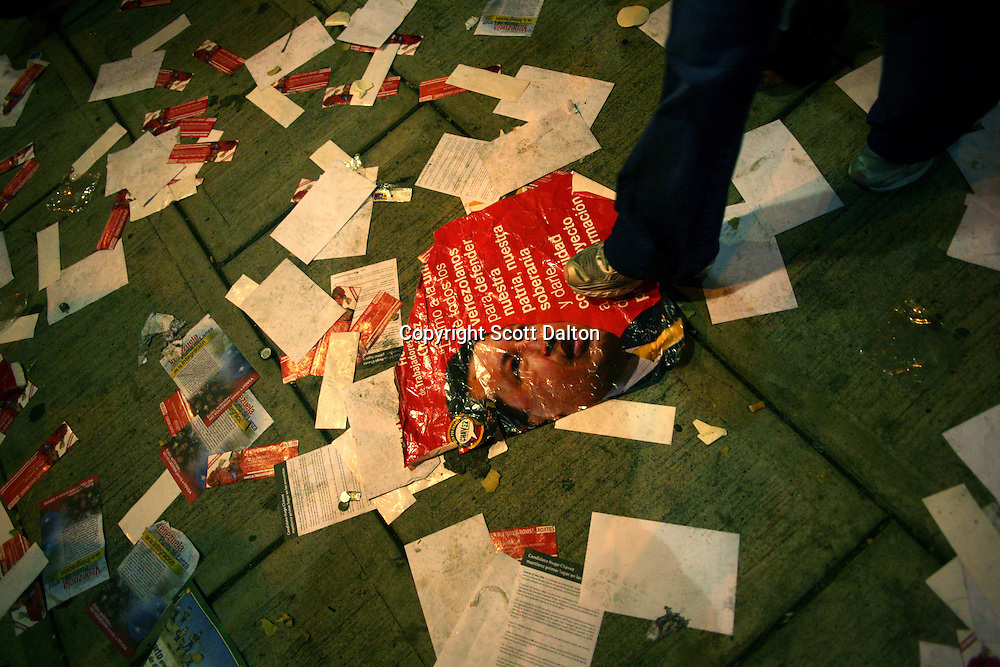 A campaign poster of President Hugo Chavez of Venezuela is among other trash on the streets at a small Chavez night rally in Caracas on Thursday, November 30, 2006. (Photo/Scott Dalton)