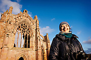 Borders Abbeys Way, Melrose Abbey, middle-aged woman smiles infront of abbey on a sunny day,