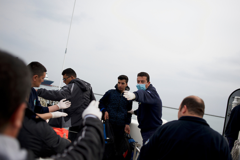 Migrants are seen been escorted out of a rescue boat arriving at Mytilene port in Lesbos island, Greece.