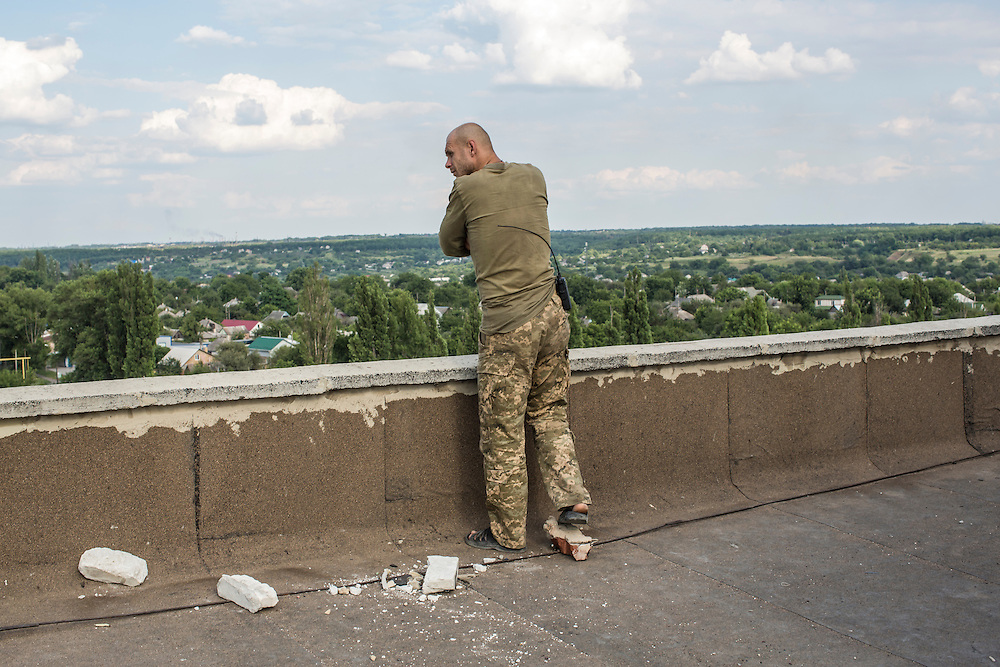 AVDIIVKA, UKRAINE - JULY 9, 2016: A Ukrainian soldier looks out from the roof of a tall residential building toward rebel-controlled territory in Avdiivka, Ukraine. The town is now one of the most active areas of fighting along the line of control between the Ukrainian government and Russian-backed rebels. CREDIT: Brendan Hoffman for The New York Times