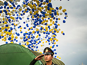 02 DECEMBER 2014 - BANGKOK, THAILAND: A Thai police officer salutes as balloons are released at the end of the Trooping of the Colors parade on Sanam Luang in Bangkok. The Thai Royal Guards parade, also known as Trooping of the Colors, occurs every December 2 in celebration of the birthday of Bhumibol Adulyadej, the King of Thailand. The Royal Guards of the Royal Thai Armed Forces perform a military parade and pledge loyalty to the monarch. Historically, the venue has been the Royal Plaza in front of the Dusit Palace and the Ananta Samakhom Throne Hall. This year it was held on Sanam Luang in front of the Grand Palace.    PHOTO BY JACK KURTZ
