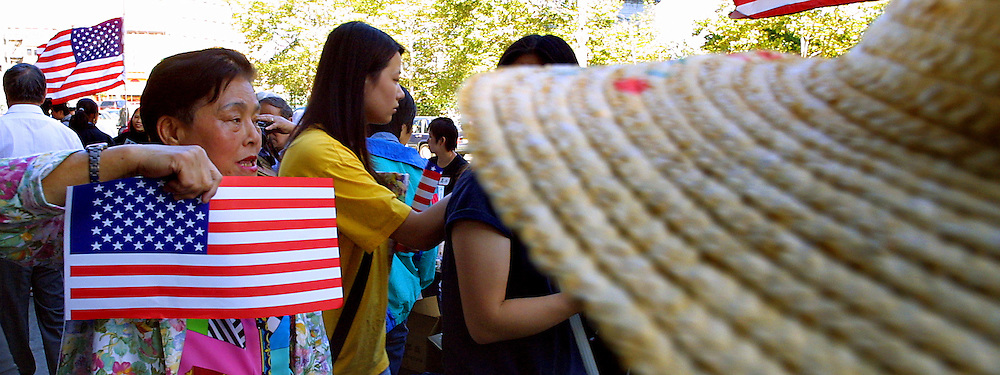 Chinatown residents sell American flags which helps to contribute cash to aid families of the disaster victims. It was an area dominated by the visage of the World Trade Center and the residents there feel the great loss.