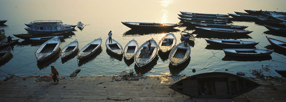 Empty boats float along the shore of the sacred Ganges river in the early morning hours.