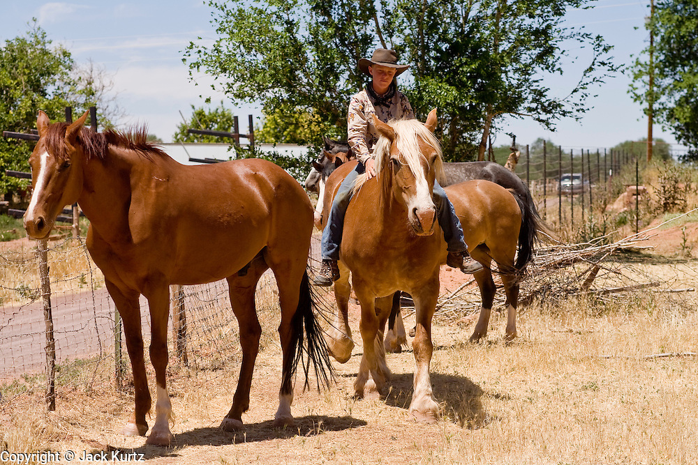 "June 16, 2008 -- COLORADO CITY, AZ: A member of the Jessop family rides his horse in the family corral in Colorado City, AZ. The Jessops are a polygamous family and members of the FLDS. Colorado City and neighboring town of Hildale, UT, are home to the Fundamentalist Church of Jesus Christ of Latter Day Saints (FLDS) which split from the mainstream Church of Jesus Christ of Latter Day Saints (Mormons) after the Mormons banned plural marriage (polygamy) in 1890 so that Utah could gain statehood into the United States. The FLDS Prophet (leader), Warren Jeffs, has been convicted in Utah of ""rape as an accomplice"" for arranging the marriage of teenage girl to her cousin and is currently on trial for similar, those less serious, charges in Arizona. After Texas child protection authorities raided the Yearning for Zion Ranch, (the FLDS compound in Eldorado, TX) many members of the FLDS community in Colorado City/Hildale fear either Arizona or Utah authorities could raid their homes in the same way. Older members of the community still remember the Short Creek Raid of 1953 when Arizona authorities using National Guard troops, raided the community, arresting the men and placing women and children in ""protective"" custody. After two years in foster care, the women and children returned to their homes. After the raid, the FLDS Church eliminated any connection to the ""Short Creek raid"" by renaming their town Colorado City in Arizona and Hildale in Utah.   Photo by Jack Kurtz"