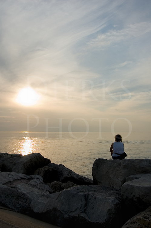 Woman in thought watching the sunset from a Great Lakes jetty.
