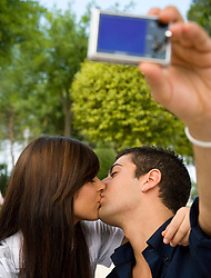 Close up of young couple kissing and taking self-portrait