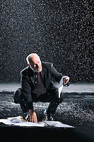 Businessman Picking up soaked Paperwork during downpour