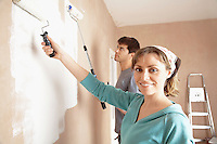 Couple using paint rollers on wall of living room