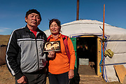 Tsatrl, a policeman, with his wife, Tsoglmaa, holding a portrait of themselves outside their ger tent on the Mongolian steppe.