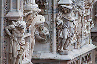 Milan, Italy, Duomo Cathedral. Exterior decoration on front of building - sculptured stone figures with intricate details.
