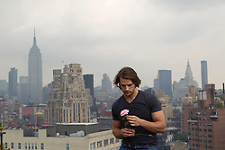 man holding a pink rose on a rooftop in New York City overlooking the Empire State Building